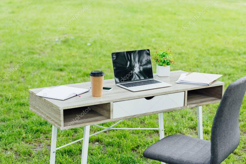 office table with different office stuff near office chair in park