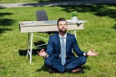 Photo businessman sitting on grass and meditating near table in park