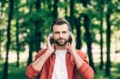 mladý muž stojící v parku, poslouchá hudbu a dívá se jinam
