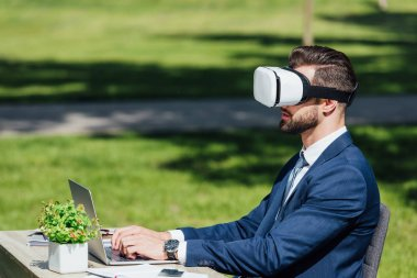 young businessman using laptop while sitting in VR headset in park