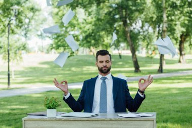young businessman sitting in park behind table and meditating near flying papers