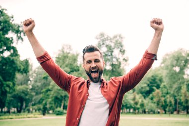excited young man standing in park and putting hands in air