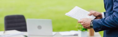 panoramic shot of man holding newspaper in park near white table with office stuff