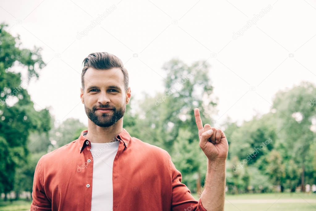 man in red shirt standing in park, looking at camera and pointing with finger