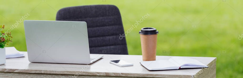 panoramic shot of table with laptop, smartphone, notebook and coffee to go near office chair in park