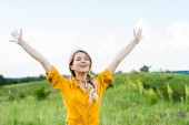 happy young woman with outstretched hands and closed eyes