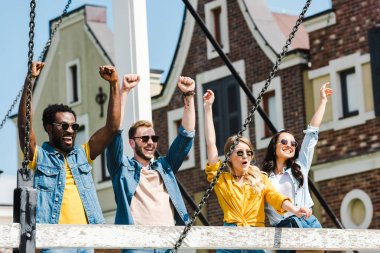 cheerful group of multicultural friends in sunglasses celebrating triumph