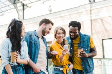 cheerful multicultural friends looking at smartphone while standing together