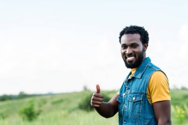 cheerful african american man standing and showing thumb up