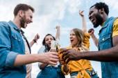 Low-Winkel-Ansicht von glücklichen multikulturellen Männern und Frauen, die Flaschen mit Bier klirren