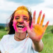 selective focus of cheerful woman with pink and yellow holi paint on face and hands