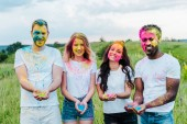 happy multicultural friends holding colorful holi paints in hands
