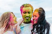 selective focus of girls with colorful holi paints on faces near african american man with closed eyes