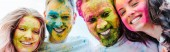 panoramic shot of happy multicultural friends with colorful holi paints on faces