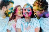happy african american man near cheerful friends with holi paints on faces