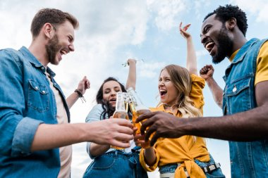 low angle view of happy multicultural men and women clinking bottles with beer