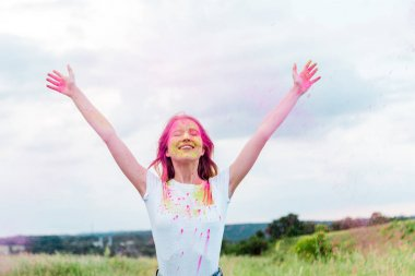 Happy woman with closed eyes and pink holi paint on outstretched hands smiling outdoors stock vector