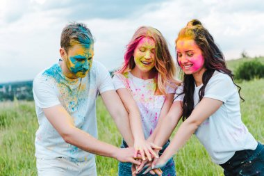 cheerful group of friends with holi paints on faces putting hands together