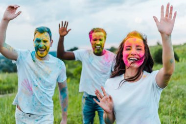 Selective focus of  multicultural friends with colorful holi paints on faces stock vector
