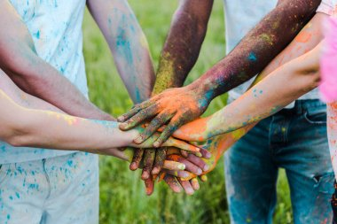 Cropped view of multicultural friends with colorful holi paints putting hands together stock vector