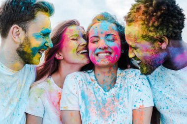 Happy african american man near cheerful friends with holi paints on faces stock vector