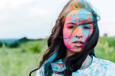 Attractive young woman with colorful holi paints looking at camera stock vector