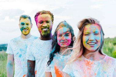 Selective focus of woman smiling near multicultural friends with holi paints on faces stock vector