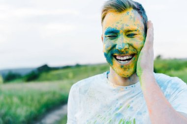 Happy young man with yellow and blue holi paints on face stock vector