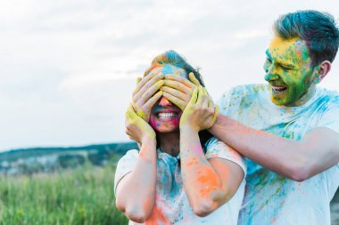 Happy young man smiling while covering face of woman with holi paints on face stock vector