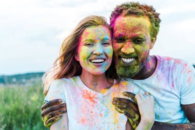Happy african american man hugging cheerful young woman with holi paints on face stock vector