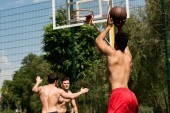 shirtless sportsmen playing basketball at basketball court in sunny day