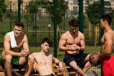 four shirtless basketball players with ball at basketball court in sunny day