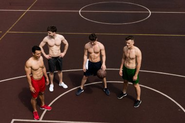 overhead view of four shirtless basketball players with ball at basketball court