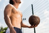cropped view of sexy shirtless sportsman holding ball at basketball court