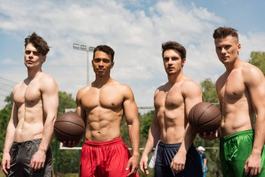 Four sexy shirtless basketball players with balls at basketball court in sunny day stock vector