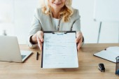 cropped view of happy woman holding clipboard in office