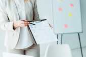 cropped view of woman holding clipboard with resume lettering and pen