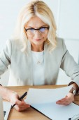selective focus of woman in glasses holding paper in office