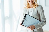 cropped view of cheerful blonde woman holding clipboard