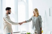 attractive blonde recruiter and handsome employee shaking hands