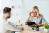 selective focus of blonde recruiter in glasses looking at clipboard near bearded man