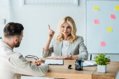 selective focus of happy recruiter gesturing near employee in office