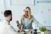 selective focus of attractive blonde recruiter holding pen and looking at bearded man