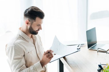 Handsome bearded man looking at paper while holding clipboard stock vector