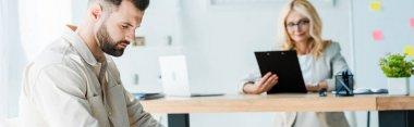 panoramic shot of upset employee sitting near attractive recruiter