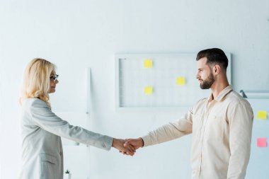 attractive recruiter in glasses and handsome employee shaking hands