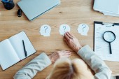 top view of blonde recruiter near paper human head shapes with question marks