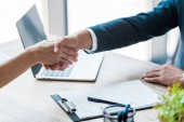 selective focus of employee and recruiter shaking hands near laptop