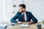 confident recruiter sitting near laptop on wooden table