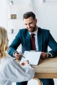 selective focus of happy recruiter holding pen near clipboard and looking at blonde employee